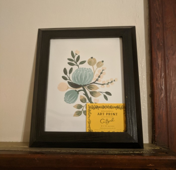 The frame sitting on a shelf containing the artwork