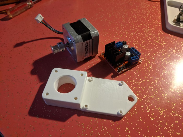 A reprinted motor arm next to a stepper motor and stepper motor driver board